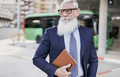 Senior business man holding digital tablet in the city with bus station in background - PhotoDune Item for Sale
