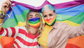 Happy lesbian women with lgbt rainbow flag at gay pride parade wearing colorful safety face mask - PhotoDune Item for Sale