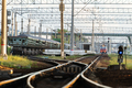 Train station platform with railway tracks at sunset and commute electric train on background. - PhotoDune Item for Sale