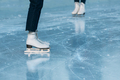 Close up of legs of ice skater on outdoor ice rink. Woman stands in white skates - PhotoDune Item for Sale
