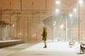 woman in hood on empty railway platform in blizzard waiting for a train. Transport delay. - PhotoDune Item for Sale
