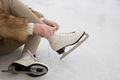 Closeup of female sitting on ice rink and tying shoelaces - PhotoDune Item for Sale