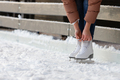 Bottom view of woman tying shoelaces, wearing white skates on ice rink in winter day. - PhotoDune Item for Sale