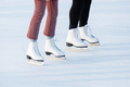 Closeup of womens legs on skates in winter on an open skating rink. Winter time, outdoors activities - PhotoDune Item for Sale