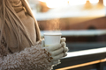 Girl hands in mittens hold steaming cup of hot coffee or tea in cold winter sunny day. Winter time - PhotoDune Item for Sale