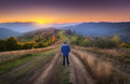 Man on the rural dirt road on the hill looking on mountain in fog - PhotoDune Item for Sale