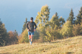 A man runs across a hilly meadow - PhotoDune Item for Sale
