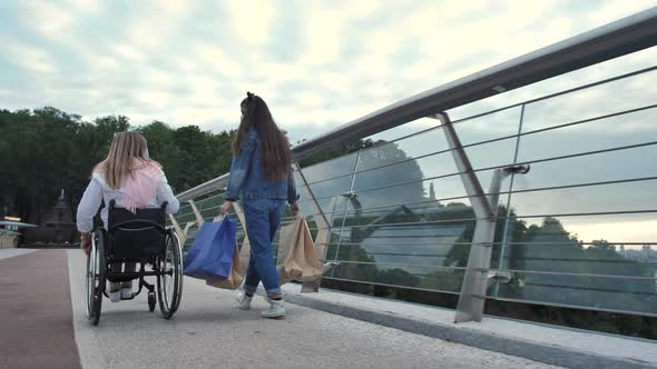 Disabled Mom with Daughter Walking After Shopping