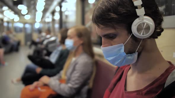 Man in Face Mask and Headphones in Metro Train
