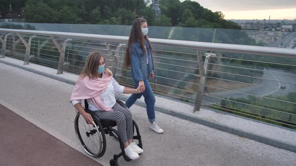 Disabled Mother with Girl in Masks Walking Outdoor