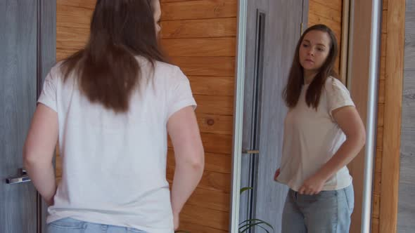 Lovely Adult Woman in Old Jeans Looking in Mirror After Successful Diet