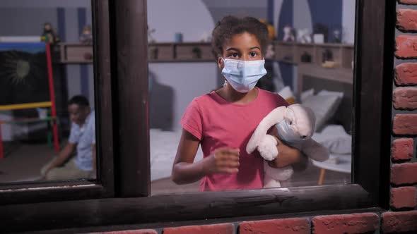 Dark-skinned Schoolgirl in Medical Mask By Window