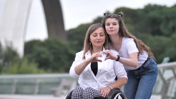 Disabled Mother and Girl Making Heart with Hands