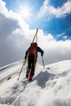 Ski mountaineer walking up along a steep snowy ridge with the skis in the backpack. - PhotoDune Item for Sale
