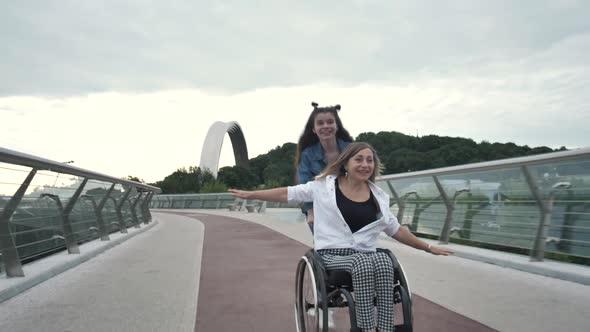 Joyful Mom with Girl Enjoying Ride on Wheelchair