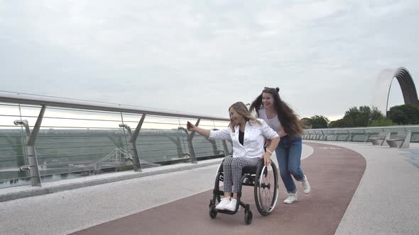 Happy Girl and Mom Filming Ride on Wheelchair