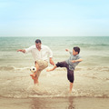 Father on the beach kicking the ball while his son tries to get - PhotoDune Item for Sale