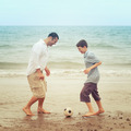 Father and son having fun on the beach and playing with a ball - PhotoDune Item for Sale