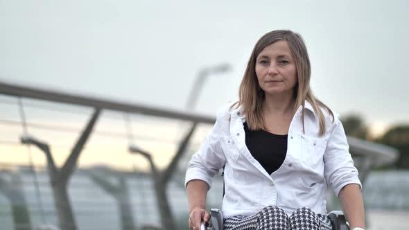 Handicapped Woman Riding Wheelchair on Footbridge
