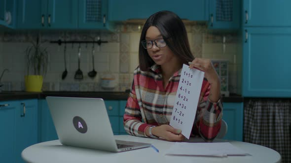 Young 20s Female African American Teacher in Glasses Talking and Showing Sheet of Paper with Simple