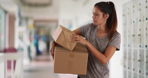 Beautiful Caucasian woman at post office with cardboard packages