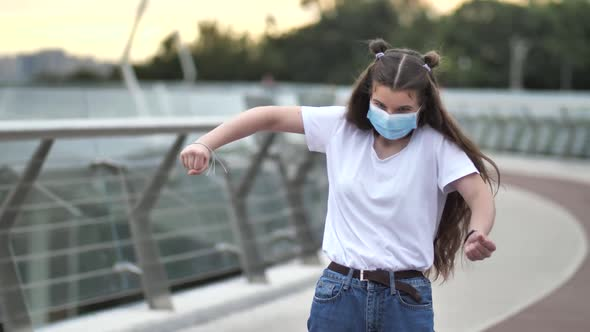Active Teenage Girl in Face Mask Dancing Outdoors