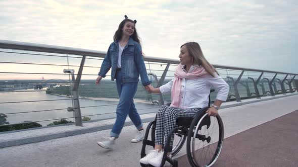 Happy Mom on Wheelchair During Walk with Daughter