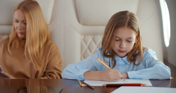 Elegant Woman Using Smartphone While Little Daughter Drawing Flying Together on Private Jet