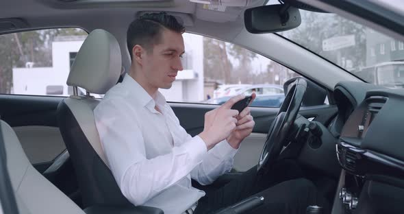 Smiling Young Man in White Shirt Playing App Game on His Smartphone While Sitting in the Drivers