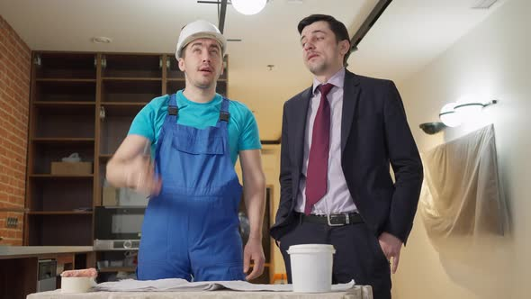 Confident Service Man Explaining Flat Renovation Plan to Young Apartment Owner