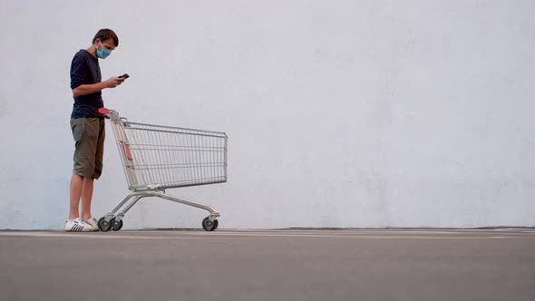 Man in Mask with Smartphone Pushing Shopping Cart. Customer with Shopping Trolley Along the Wall of