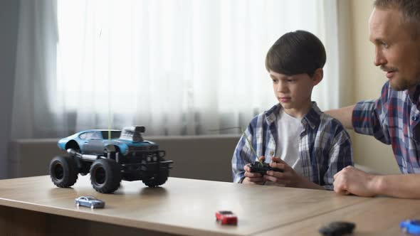 Cute Kid and His Father Operating Radio Controlled Car at Home, Technologies