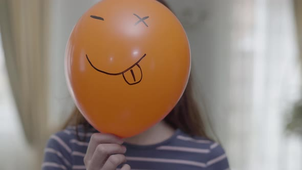 A Funny Girl Hold Orange Baloon with Emoji and Making Same Emoji Face with Wink Emoticon