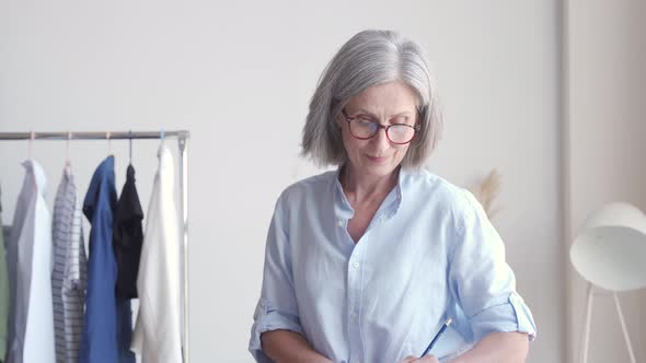 Middle Aged Elegant Woman Fashion Designer Drawing Sketches on Table