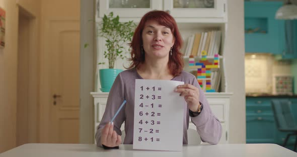 40s Female Teacher Talking To Camera and Holding Sheet of Paper with Simple Mathematical Equations